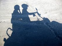 Shadow from a young pair on the motor scooter Royalty Free Stock Images