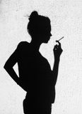 Shadow of young woman smoking around on wall background Royalty Free Stock Images