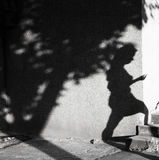 Shadow of a young woman walking up stairs. Around the corner on city street on a hot summer day in black and white Royalty Free Stock Photography