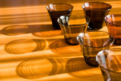 Shadowed glasses on the wood table. Stock Images