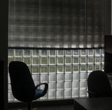 Shadowed Office Chairs Waiiting At Dawn With Glass Block Windows. In a square pattern while light slowly prepares there use Royalty Free Stock Photography