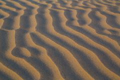 Shadowed sand ripples close up in soft light. Abstract background royalty free stock photography