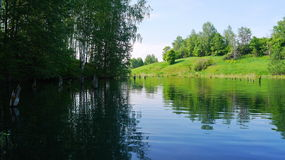 Shadowed and sunny parts of the forest lake. Taken from boat Royalty Free Stock Photo
