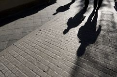 Shadows. Of people walking along a cobblestone street, Seville, Andalucia, Spain stock photos