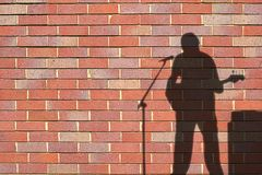 Shadows. Of guitarist against wall royalty free stock photos