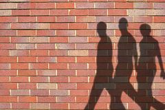 Shadows. Of men against wall stock photo