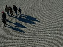 Shadows. People in silhouette against a stone brick floor Stock Photos