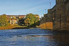 Shadows across the river. Historic Corbridge bridge across the river Tyne showing shadows of the bridge and the town with trees in autumn colors Royalty Free Stock Photo
