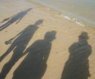 Shadows on the beach. Shadows of four persons on the beach Stock Photo