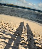 Shadows on a beach. A picture of the shadow of two people holding hands on a tropical island beach in the carribean Royalty Free Stock Images