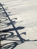 Shadows of bicycle on paving slabs stock images