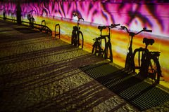 Shadows of bicycles. Color illuminated wall with shadows of bicycles Stock Photo