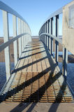 Shadows on the bridge. Bridge on beach looking at walkway with shadows cast on the metal and sand and sea in background Stock Image