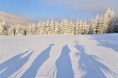 Shadows cast by hikers. Shadows cast on the snow by people in mountains stock images