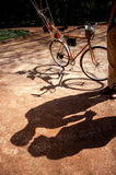 Shadows of  couple standing in the park alley with bicycle and a Stock Photo