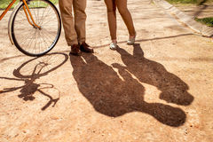 Shadows of  couple standing in the park alley with bicycle and a. Irship on it on the background Stock Images
