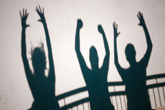 Shadows of ecstatic people. Creative photo of ecstatic people shadows on white wall stock photos