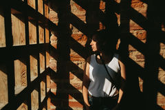 Shadows fall through the gate on the woman near brick wall Stock Image