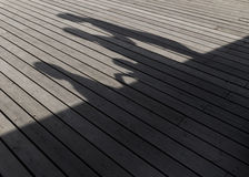 Shadows of a family walking on a wooden plank Stock Image