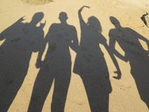 Shadows of five young peole having fun on the beach on Cyprus royalty free stock photography