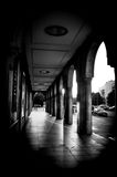 Shadows on floor through building with arches in black and white Stock Photography