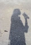 Shadows of girl are drinking water on the street background Royalty Free Stock Images