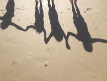 4 shadows. Of girls holding hands at beach jumping Royalty Free Stock Photo