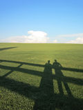 Shadows on grass. Shadows of two people on a grassy field Royalty Free Stock Photo