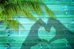 Shadows of hands forming a heart on summer background with palm trees. Shadows of hands forming a heart on blue summer background with palm trees Royalty Free Stock Photos