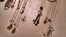 Shadows. Hanging necklaces making shadows against the wall Stock Images