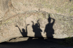 Shadows of happy people with arms raised on rock. In sunny day Stock Photography