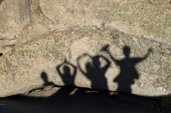 Shadows of happy people with arms raised on rock. In sunny day Royalty Free Stock Photo