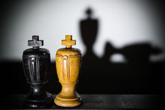 Shadows of king pieces with one lying Stock Image