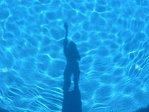 Shadows in the light blue swiming pool. Human figure shadows in the light blue swiming pool Stock Photos