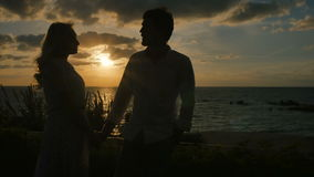 Shadows of lovely couple at the sunset background. Lovely couple of two young people are standing at the sunset background. The lovers holds hands and talking stock video footage