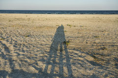 Shadows of loving couple. Long shadow of young couple holding hands cast on beach sand stock images