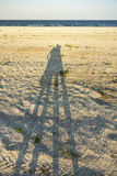 Shadows of loving couple. Long shadow of young couple holding hands cast on beach sand royalty free stock photos