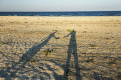 Shadows of loving couple. Long shadow of young couple holding hands cast on beach sand royalty free stock photography