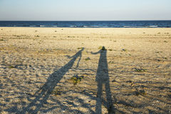 Shadows of loving couple. Long shadow of young couple holding hands cast on beach sand royalty free stock images