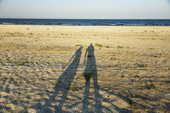 Shadows of loving couple. Long shadow of young couple holding hands cast on beach sand stock photo