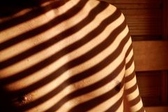 Shadows on man chest. Regular stripes of shadow on chest of a man Royalty Free Stock Photo