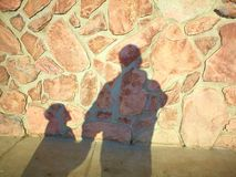 Shadows of memories. Shadows of child and mother at old rock wall stock photos