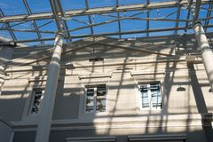 Shadows from a metal roof structure on an old modernized building. On a sunny day royalty free stock photo