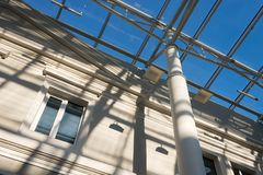 Shadows from a metal roof structure on an old modernized building. On a sunny day stock photo