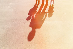 Shadows of mother with son and daughter holding. Hands on the road royalty free stock images