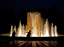 SHADOWS IN THE NIGHT PEOPLE LIGHT AND FOUNTAIN Royalty Free Stock Photography
