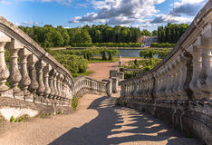 Shadows of old stairs to green garden under blue sky with bulky clouds in summer Petergof Stock Photo
