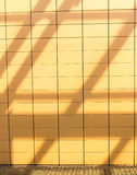 Shadows on orange tiled wall background. Blank copyspace. Real. Royalty Free Stock Image