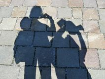 Shadows on a path of tourists taking photos. Shadows on a stone block walkway of two tourists taking photographs Royalty Free Stock Photo