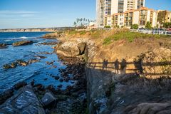 Shadows of people on bridge appear on bluff at Pacific Ocean at La Jolla Beach, San Diego stock photos